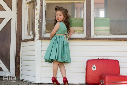 children's photography, children's portraits, young girl at train station with luggage in a green dress with vintage hair