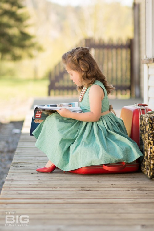 children's photography, birthday portraits, young girl in a green dress with rockabilly hair waiting at train station reading a magazine