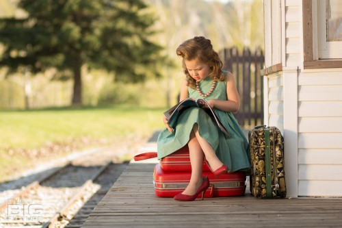 children's photography, kid's portraits, little girl sitting on suitcases at the train station reading a magazine with vintage hair