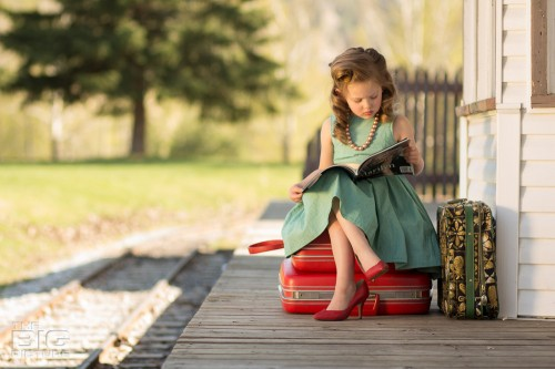 children's photography, vintage children's portraits, little girl sitting on suitcases reading a marilyn monroe magazine at a railway station