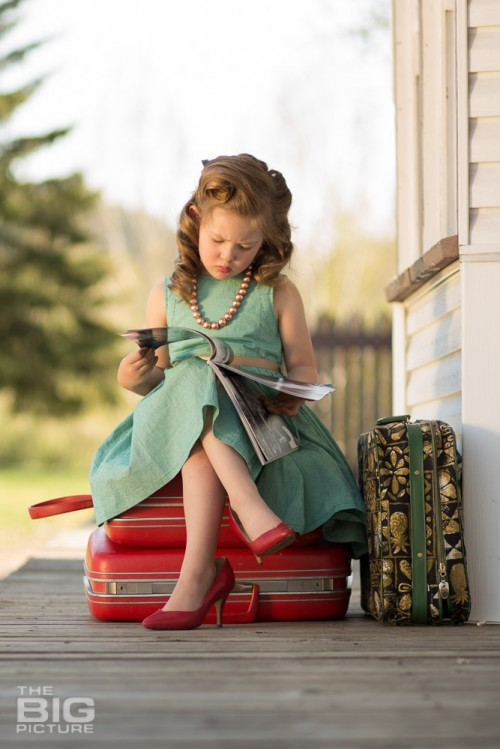 childrens photography, little girl at the train station in high heels reading a magazine, vintage hair, retro kids photos
