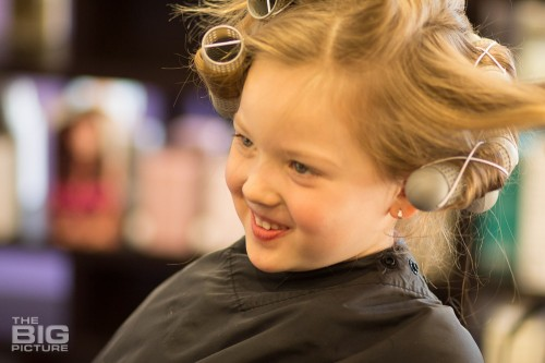children's photography, young girl in a salon with curlers in her hair smiling, retro children