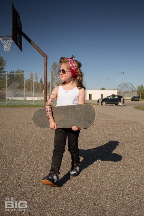 children's portraits, little skater girl with sunglasses and retro hair and fake tattoo sleeve carrying a skateboard in a skate park on a sunny day, children's photography, skater girl