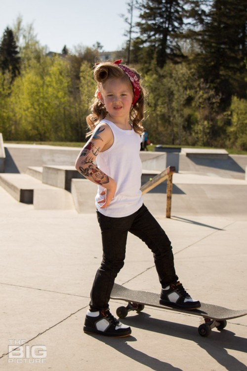 children's portraits, little skater girl with retro hair and fake tattoo sleeve standing on a skateboard in a skate park on a sunny day, children's photography, skater girl