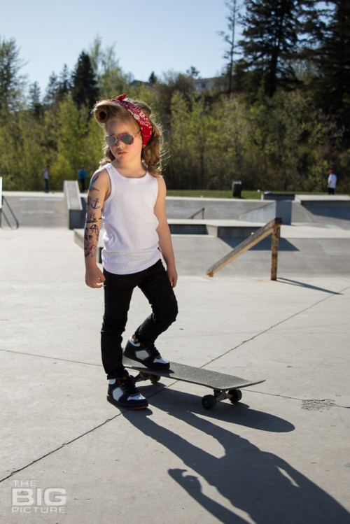 children's portraits, little skater girl with sunglasses on retro hair and fake tattoo sleeve standing on a skateboard in a skate park on a sunny day, children's photography, skater girl