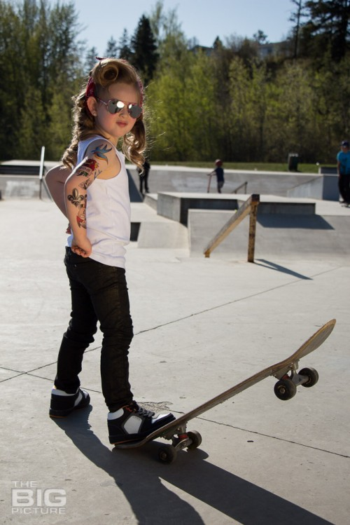 children's portraits, little skater girl with sunglasses and retro hair and fake tattoo sleeve standing on a skateboard with her hands on her hips in a skate park on a sunny day, children's photography, skater girl