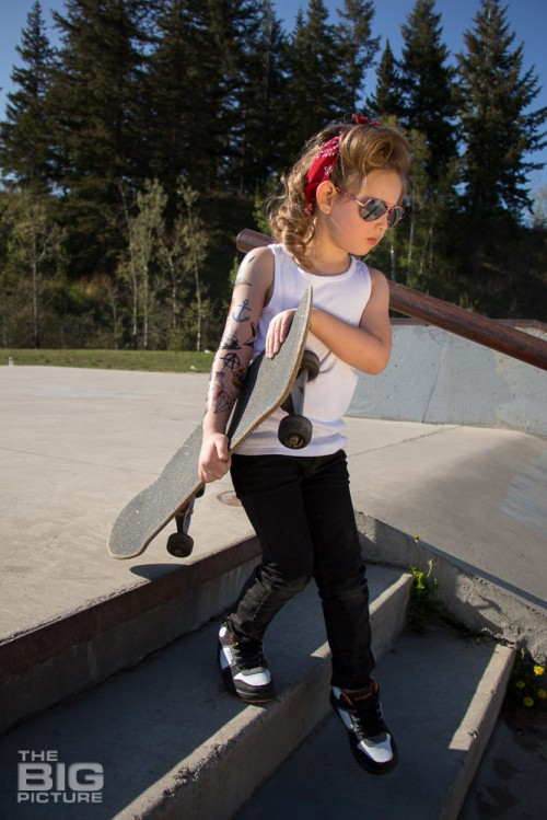 children's portraits, little skater girl with sunglasses and retro hair and fake tattoo sleeve holding a skateboard going down stairs in a skate park on a sunny day, children's photography, skater girl