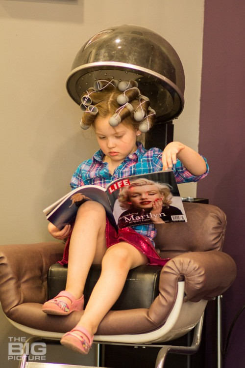 children's photography, young girl with curlers in her hair under a hair dryer looking at a Marilyn Monroe magazine, life magazine, kid's retro hair, vintage rockabilly