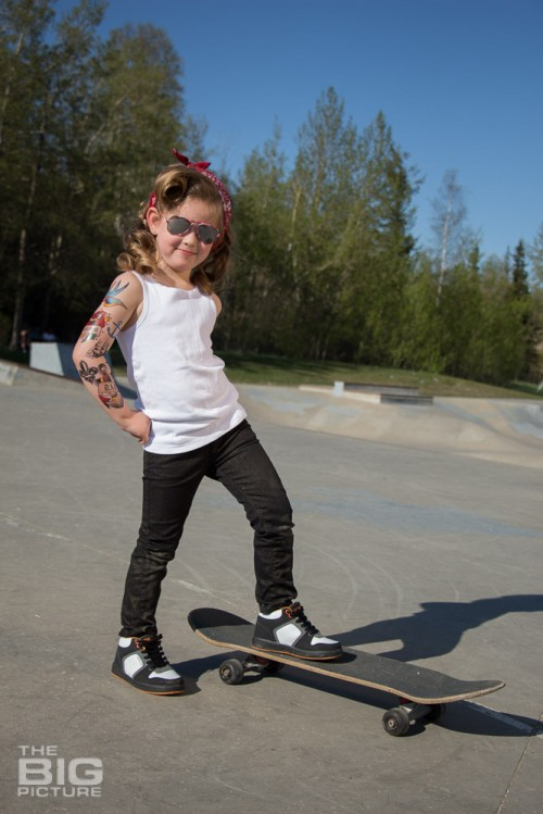 children's portraits, smiling little skater girl wearing sunglasses with retro hair and fake tattoo sleeve standing on a skateboard in a skate park on a sunny day, children's photography, skater girl