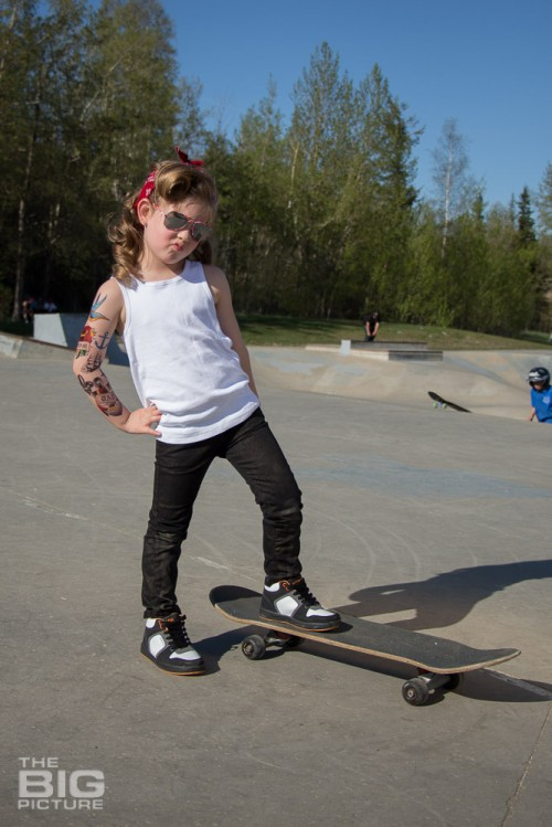 children's portraits, little skater girl making a duck face wearing sunglasses with retro hair and fake tattoo sleeve standing on a skateboard in a skate park on a sunny day, children's photography, skater girl