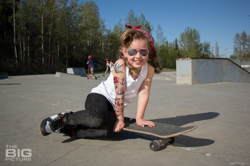 children's portraits, smiling little skater girl wearing sunglasses with retro hair and fake tattoo sleeve sitting on a skateboard in a skate park on a sunny day, children's photography, skater girl