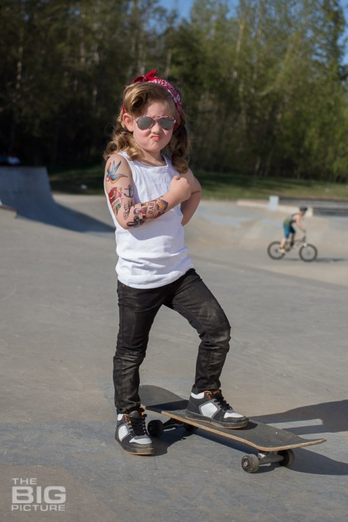 children's portraits, smiling little skater girl wearing sunglasses with retro hair and fake tattoo sleeve standing on a skateboard flexing her muscles in a skate park on a sunny day, children's photography, skater girl