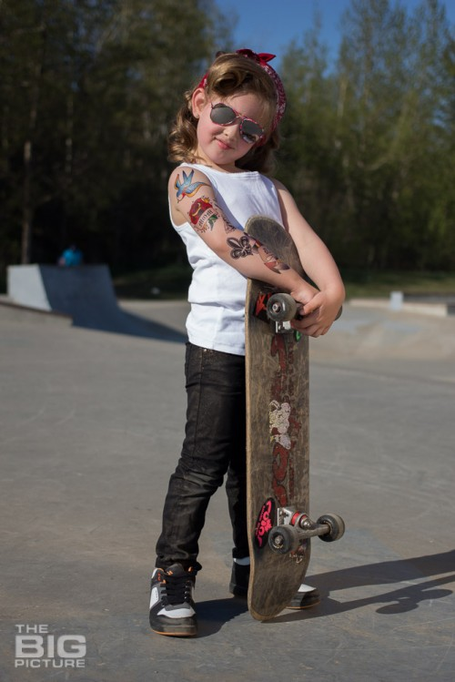 children's portraits, smiling little skater girl wearing sunglasses with retro hair and fake tattoo sleeve holding a skateboard in a skate park on a sunny day, children's photography, skater girl