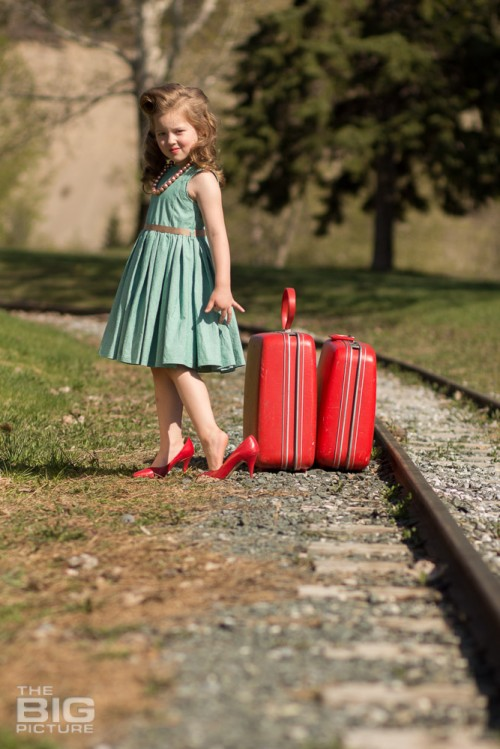 children's portraits, young girl with victory rollsl in red high heels with red luggage by railroad tracks
