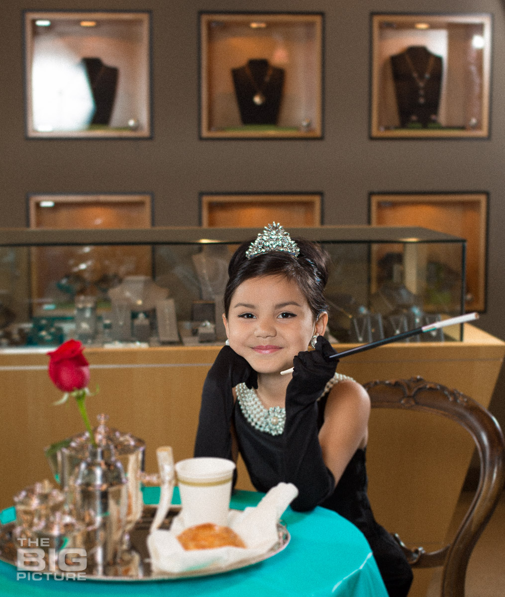 Children's Photography - Kids Photography - Ava sitting at the table in a jewellery shop