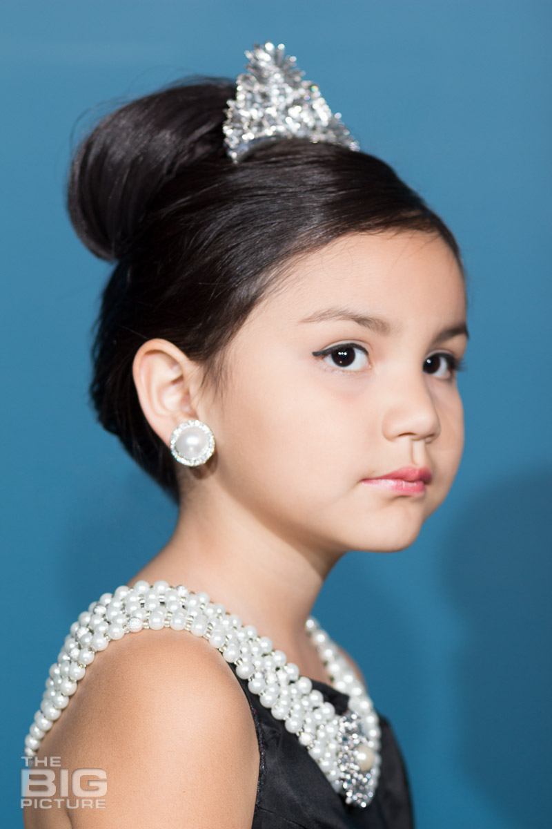 Ava dressed up like Audrey Hepburn in a scene from breakfast at Tiffany's - wearing pearls and a tiara  - kids photography - children's photography